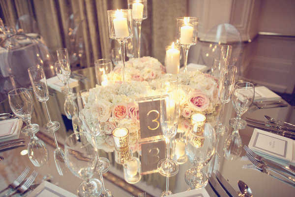Mirrored table tall candles votive candles white and pink flowers