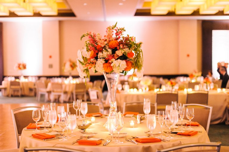 It's a great idea to incorporate a mix of high and low centerpieces; it helps break up the room and adds sophistication. Photo Credit: Krista A. Jones Photography